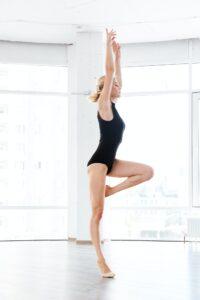 Woman ballerina in leotard dancing in dance class
